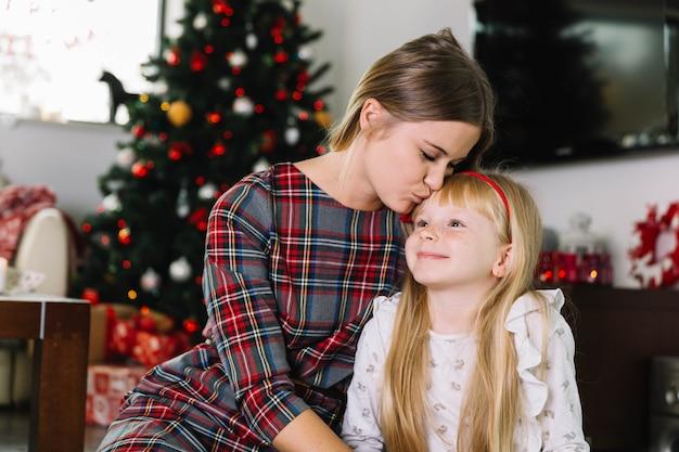 Moeder kussende dochter voor kerstmisboom