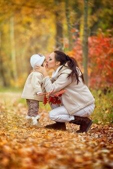 Moeder kust een kleine dochter in een tuit, herfstpark.