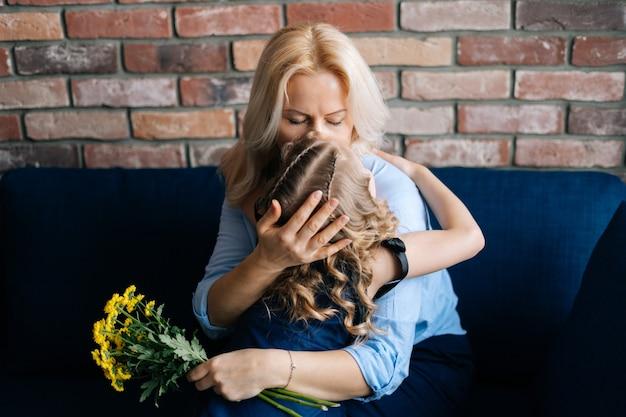 Moeder kust en knuffelt haar dochtertje dat haar een boeket bloemen heeft gegeven