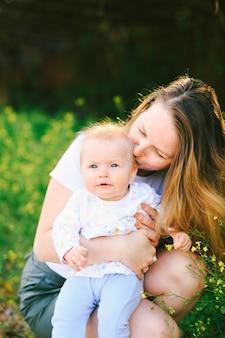 Moeder kust haar babymeisje zittend op het gazon