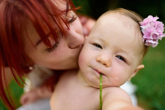 Moeder kust haar eenjarig meisje op de wang. het meisje knijpt haar ogen samen. detailopname.