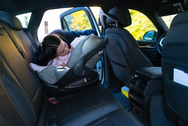 Moeder kuste haar baby in babyzitje op de achterbank van de auto met zwart interieur, gezien vanaf de andere kant van het voertuig met kopie ruimte