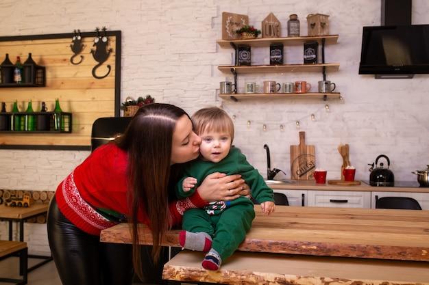 Moeder kuste haar babyjongen in de keuken van kerstmis thuis