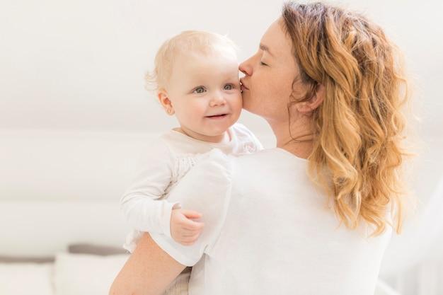 Moeder kuste haar schattige babymeisje