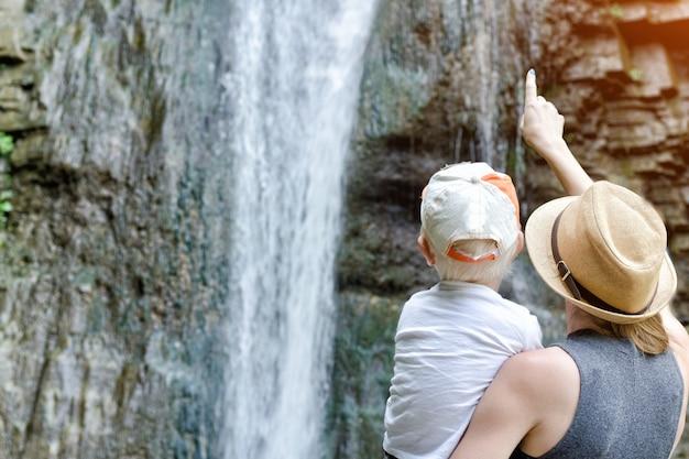 Moeder laat zijn zoon een waterval zien, een uitzicht vanaf de achterkant.