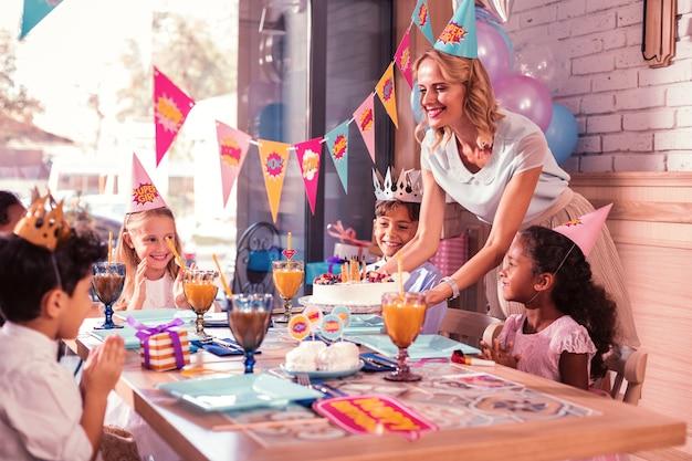 Moeder lacht en brengt de verjaardagstaart voor kinderen