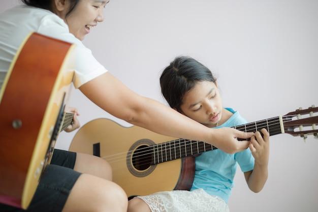 Moeder leert de dochter leren hoe ze akoestische klassieke gitaar spelen voor jazz en gemakkelijk luisteren lied selecteren focus ondiepe scherptediepte