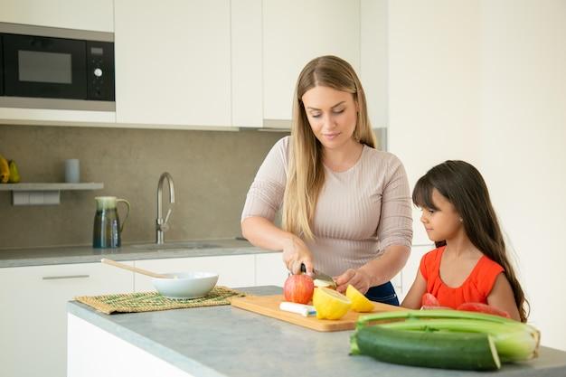 Moeder leert dochter koken. meisje en haar moeder samen koken, vers fruit en groenten snijden op snijplank in de keuken. familie koken concept