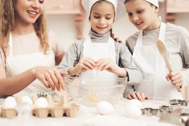 Moeder leert dochter om egg domestic bakery te breken.