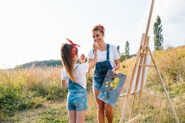 Moeder leert dochter verf in park. zonnige natuur, moeder en dochter schilderen een foto in een park, schilderen een klein kind, kindercreativiteit.