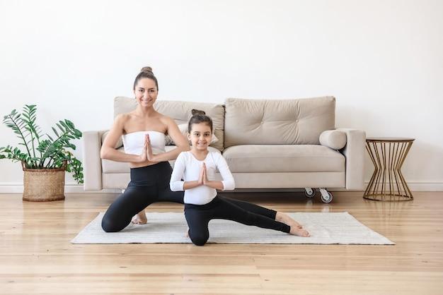 Moeder leert dochter yoga thuis in de woonkamer tijdens het sporten