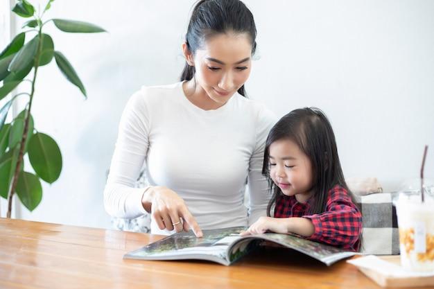 Moeder leert haar dochter een boek lezen.