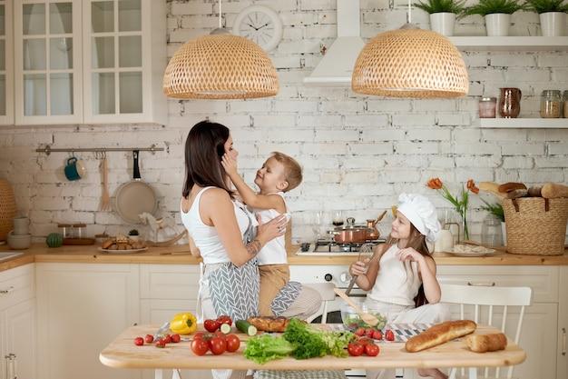 Moeder leert haar dochter en zoon een salade met verse groenten te bereiden