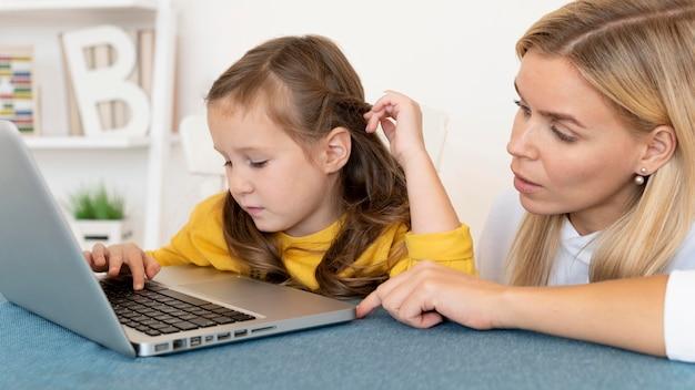 Moeder leert haar dochter hoe ze laptop moet gebruiken