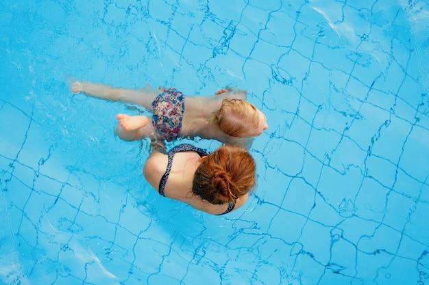 Moeder leert haar dochter jaar oud om te zwemmen in het bovenaanzicht van het zwembad