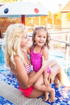 Moeder leert haar dochter zwemmen in het zwembad