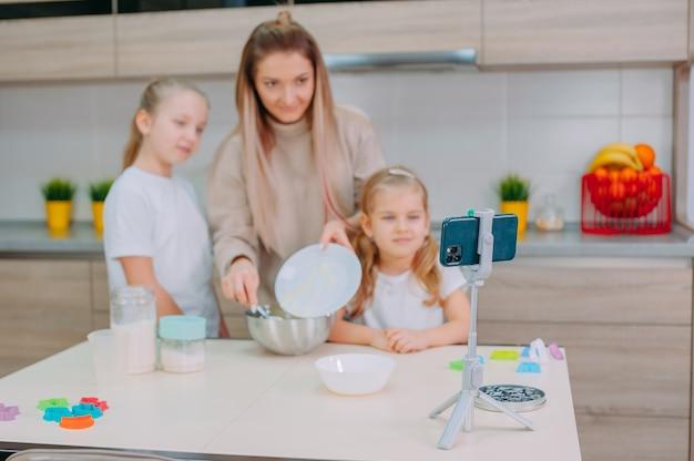 Moeder leert haar dochters deeg koken in de keuken.