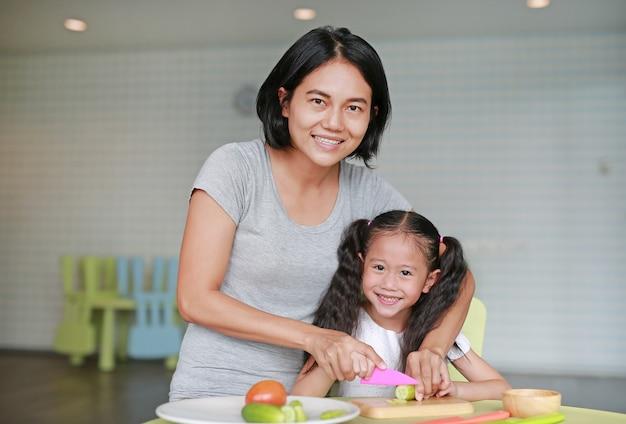 Moeder leert haar kinderen koken. sluit omhoog aziatische mamma en dochter snijdende komkommergroente op hakbord bij spelruimte.