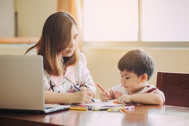 Moeder leert haar zoon huiswerk te maken concept voor thuisonderwijs en onderwijs