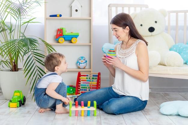 Moeder leert het kind thuis door educatief speelgoed te spelen in de kinderkamer. een gelukkig, liefdevol gezin.