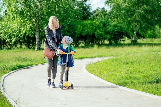 Moeder leert het kind (zoon) jongetje om op een scooter te rijden in een park op een achtergrond van groen gras en bomen
