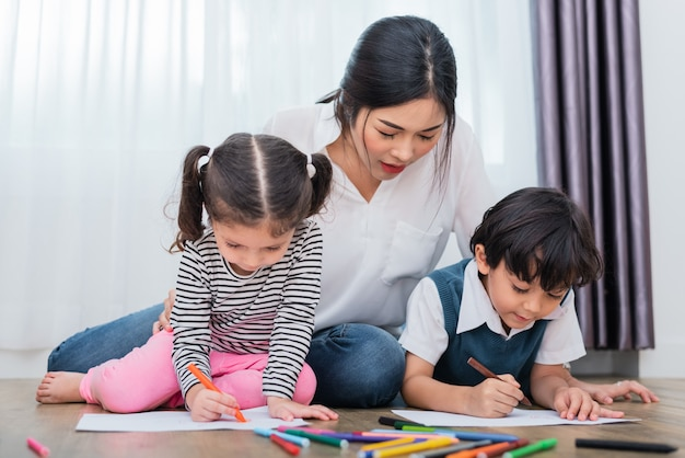 Moeder leert kinderen in tekenles. het schilderen van de dochter en van de zoon met kleurpotloodkleur binnen