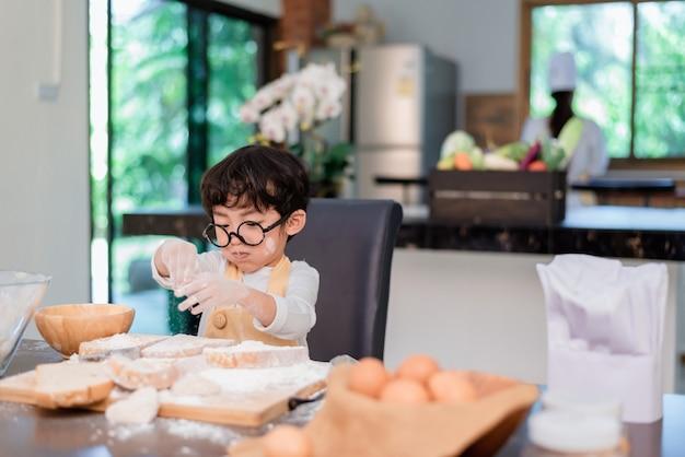 Moeder leert zoon om voedsel te koken. moeder en kind dagelijkse levensstijl thuis. aziatische familie samen in de keuken.