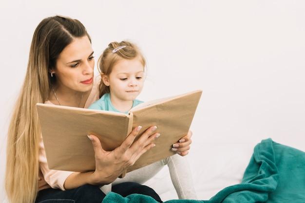 Moeder leesboek schattig meisje op bed