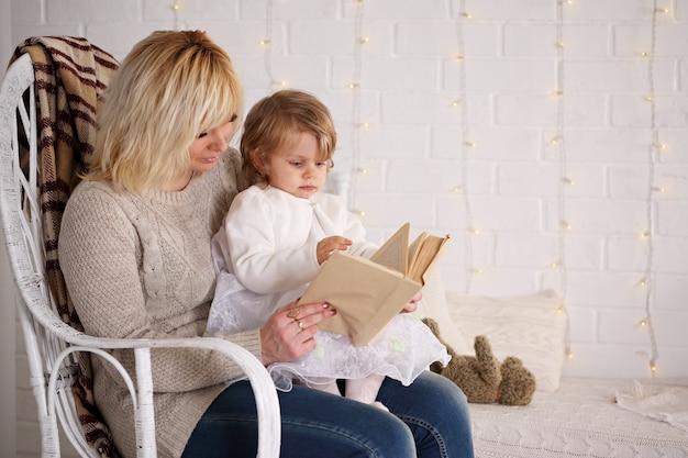 Moeder leest een boek aan een dochter die in een rieten stoel zit