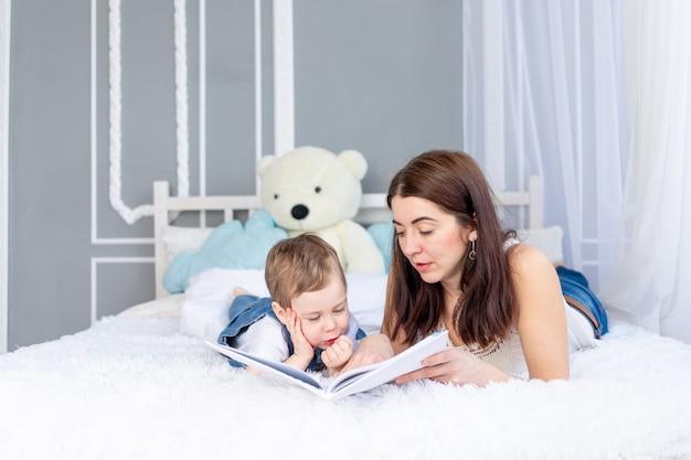 Moeder leest een boek voor aan het kind of leert hem thuis op het bed gelukkige liefdevolle familie. moeder en zoon.