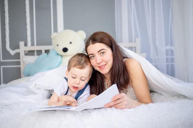 Moeder leest een boek voor het kind of leert hem thuis op het bed gelukkig liefdevol gezin. moeder en zoon