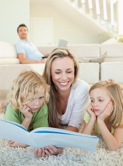 Moeder leestijdschrift met haar kinderen op de vloer