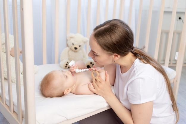 Moeder legt baby te slapen in de wieg of geeft hem een knaagdier, gelukkig gezin