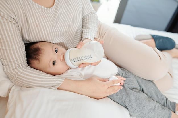 Moeder liggend in bed en haar dochtertje voeden met formule in een fles
