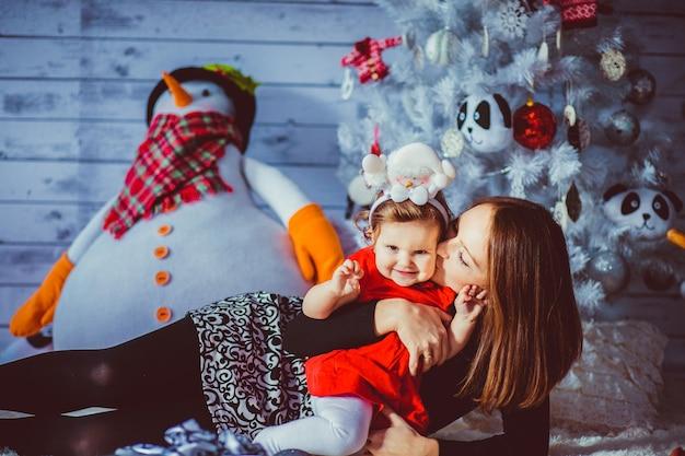 'moeder liggend op tapijt knuffel dochter'