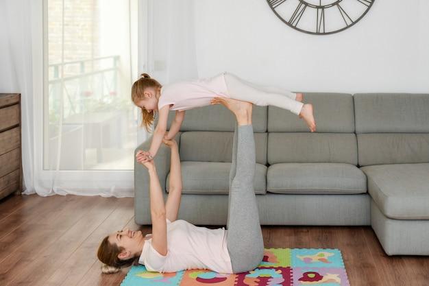 Moeder ligt op een ontwikkelingsmat voor kinderen en doet yoga vogeltje met haar dochter. blijf thuis