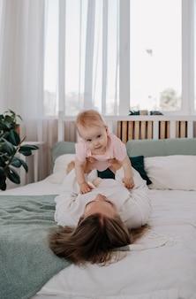 Moeder ligt op het bed en tilt het meisje op