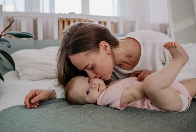 Moeder ligt op het bed met een babymeisje op het bed in de kamer en kust