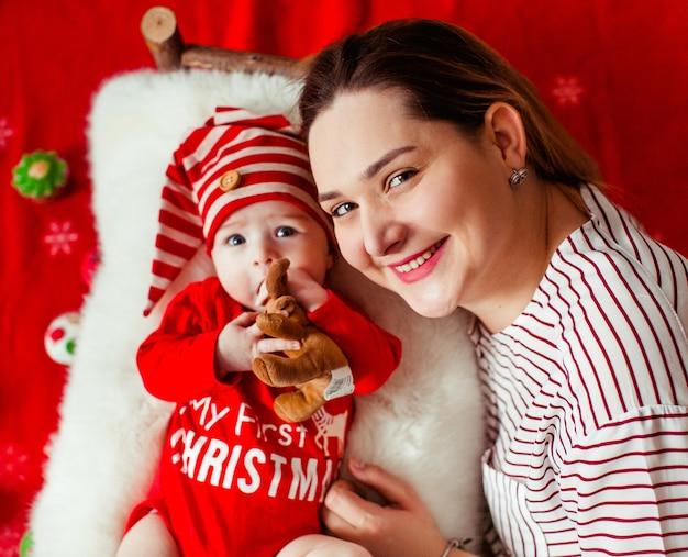 Moeder ligt voor haar grappige dochter in een rood pak met opschrift 'my first christmas'