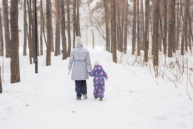 Moeder loopt met haar dochtertje in besneeuwde park, achteraanzicht.