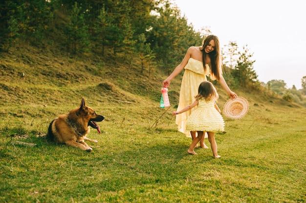Moeder loopt met zijn dochtertje en hun hond