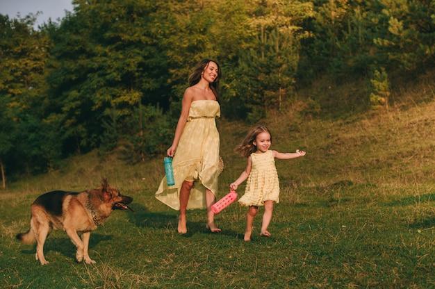 Moeder lopen met zijn dochtertje en hun hond