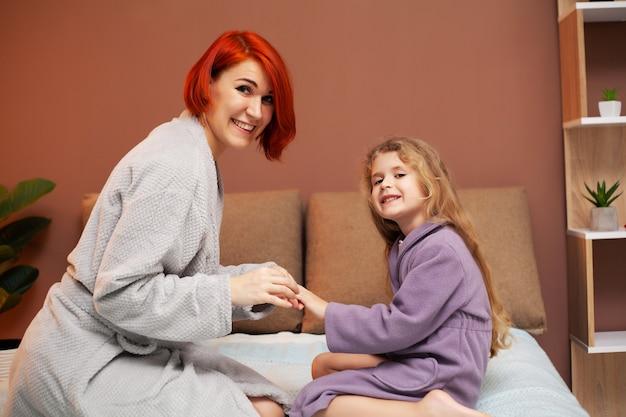 Moeder maakt dochter op het bed thuis manicure