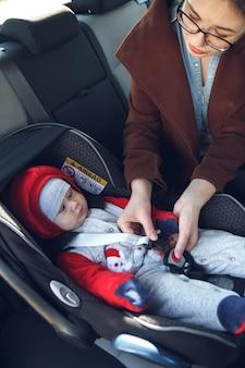 Moeder maakt een veiligheidsgordel vast in het autostoeltje waarin haar kleine kind zit
