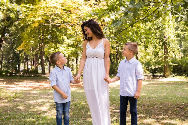 Moeder maakt een wandeling in het park met haar zonen
