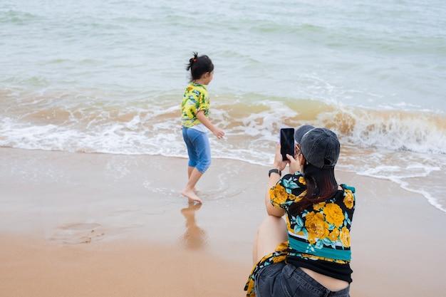 Moeder maakt foto's van haar dochter op het strand.