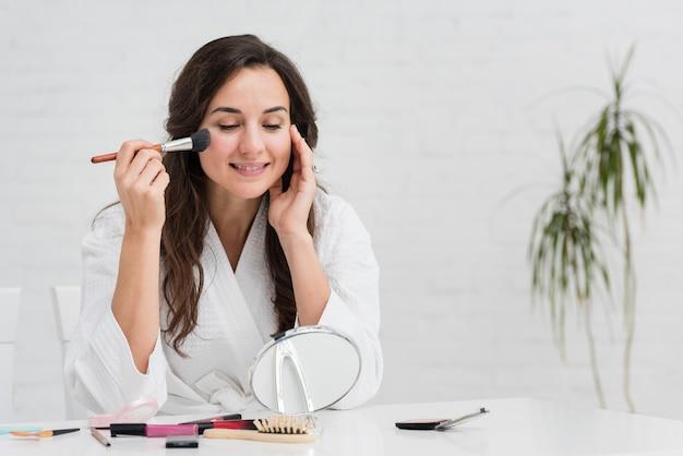 Moeder maakt zich op voor een nieuwe dag door haar make-up op te doen