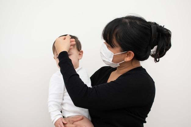 Moeder maakt zich zorgen over haar zoon die ziek wordt, raak zijn voorhoofd aan om het te controleren.