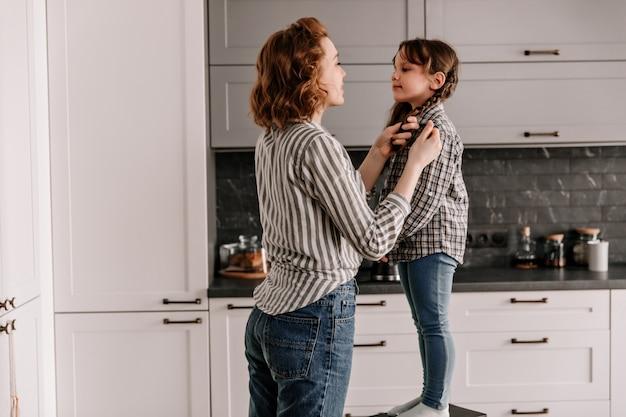 Moeder maakt zorgvuldig het haar van haar dochter vast, staande op een stoel.