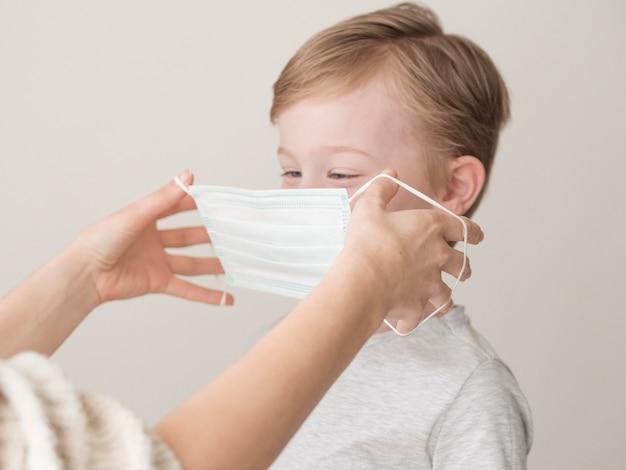 Moeder masker op jongen zetten